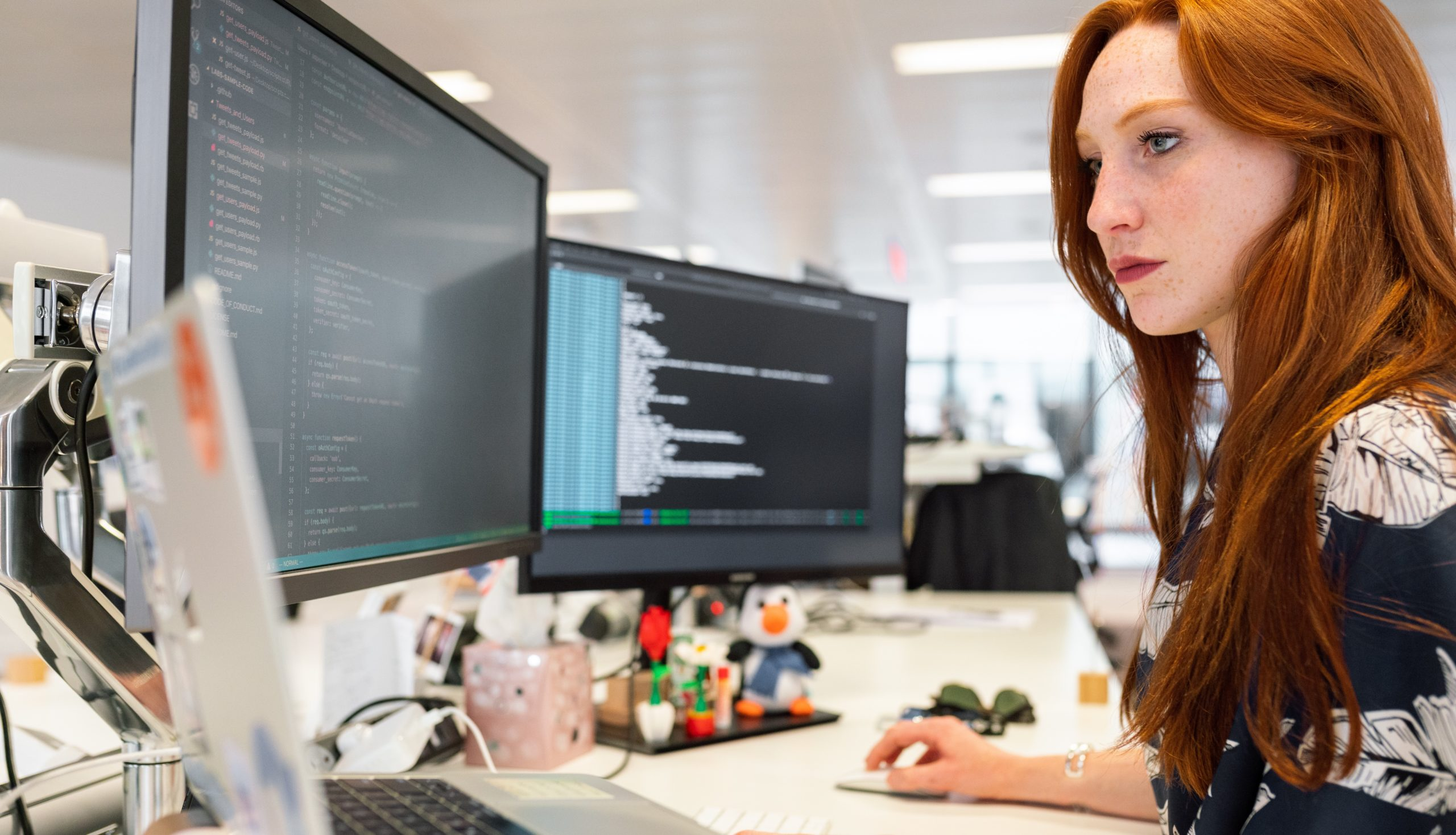 Young Woman in front of Monitors Writing Code