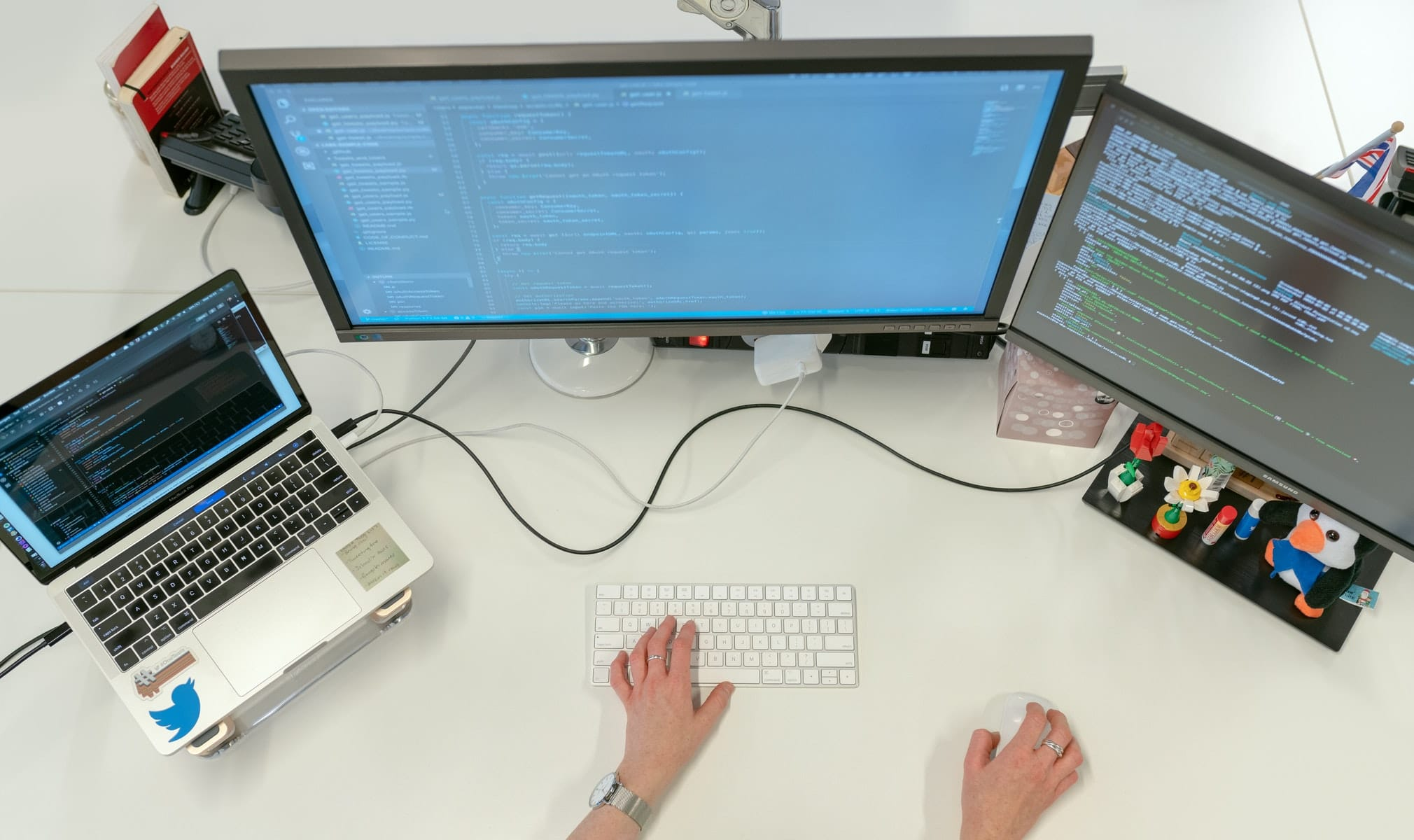 A woman in front of three computer monitors