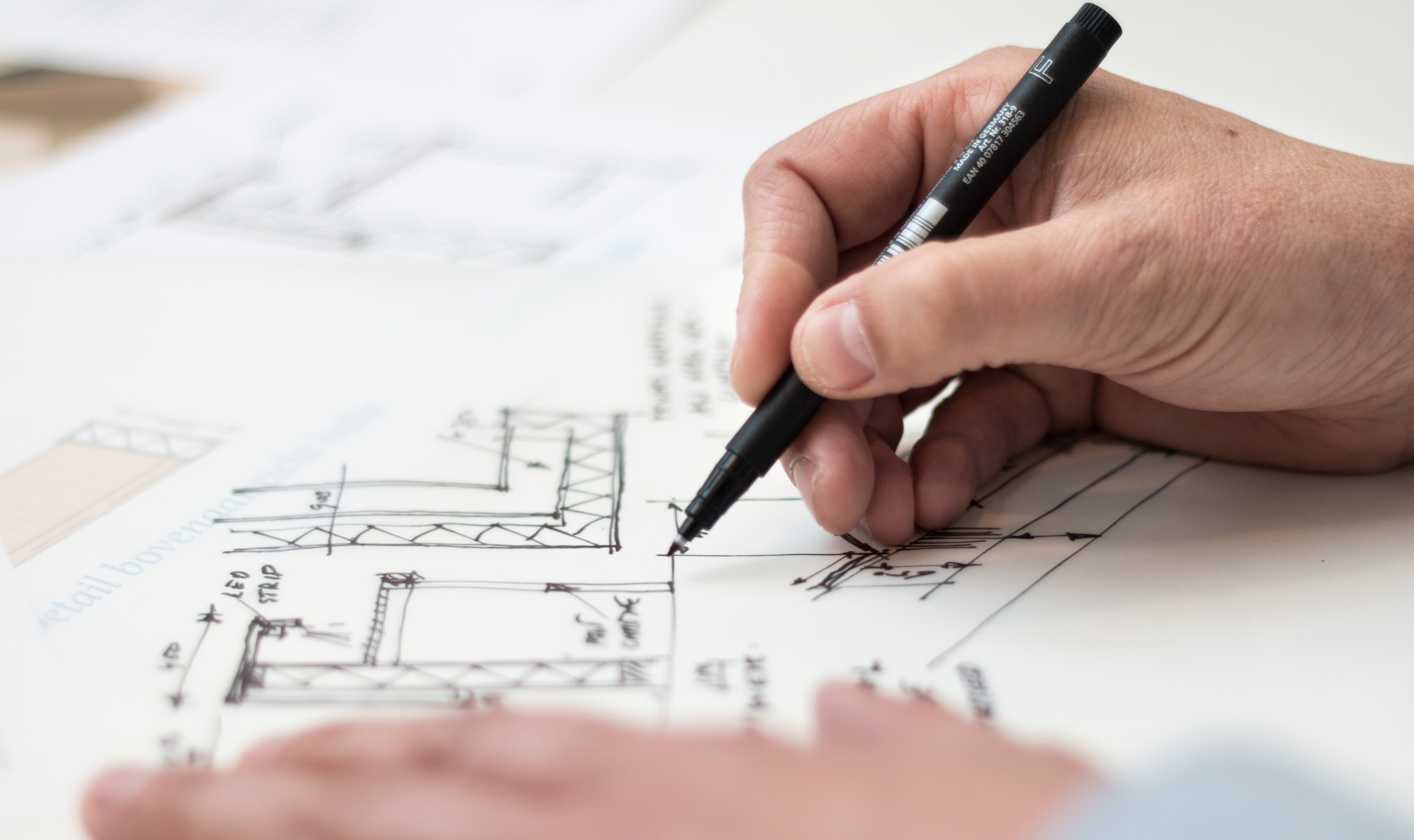 A man writing some kind of blueprints